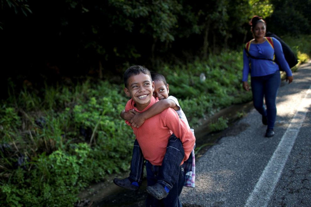 PHOTO: Denzel, 8, holds his brother Adonai, 5, near their mother Glenda Escobar, a migrant from Honduras, part of a caravan of thousands from Central America en route to the United States, as they walk to Pijijiapan from Mapastepec, Mexico, Oct. 25, 2018.
