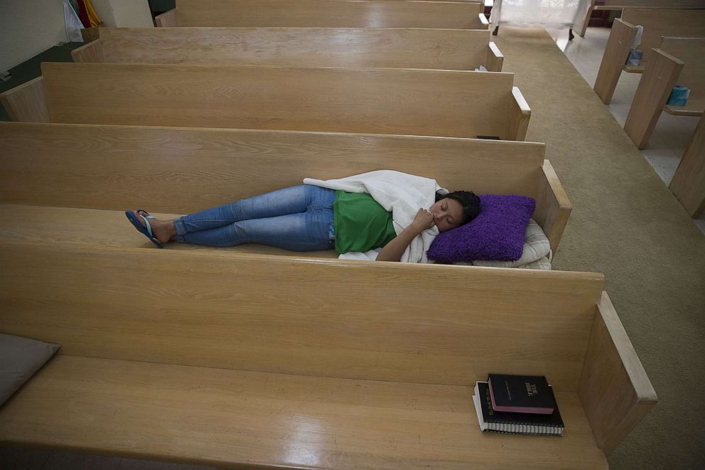 PHOTO: A woman originally from Guatemala sleeps on a pew bench at the El Calvario Methodist Church, after she was released by the U.S. Immigration and Customs Enforcement, June 3, 2019 in Las Cruces, New Mexico.