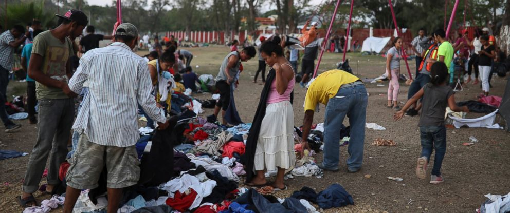 Central American migrants participating in the Migrant Stations of the Cross caravan search through donated clothing during the caravans few-days stop at a sports center in Matias Romero, Oaxaca state, Mexico, late Monday, April 2, 2018.