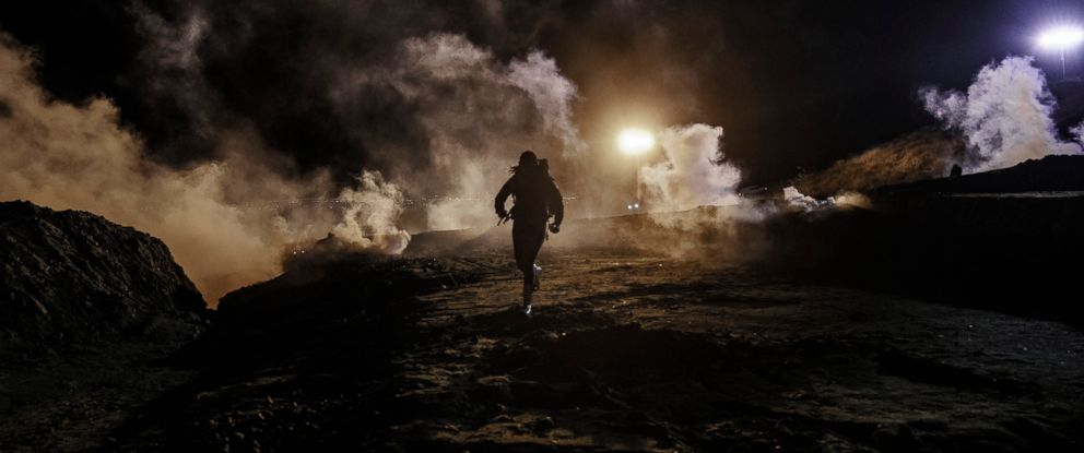 PHOTO: Migrants run as tear gas is thrown by U.S. Border Protection officers to the Mexican side of the border fence after they climbed the fence to get to San Diego, Calif., from Tijuana, Mexico, Tuesday, Jan. 1, 2019.