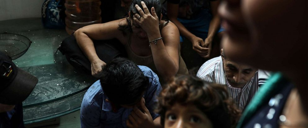 PHOTO: Detained migrants stand together in a storage room at the back of the Azteca Hotel where they tried to hide from Mexican immigration agents conducting a raid in Veracruz, Mexico, June 27, 2019.