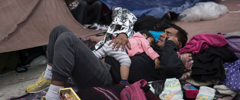 A migrant father and child, who traveled with the annual caravan of Central American migrants, rest where they set up camp to wait for access to request asylum in the US, on Monday, April 30, 2018.