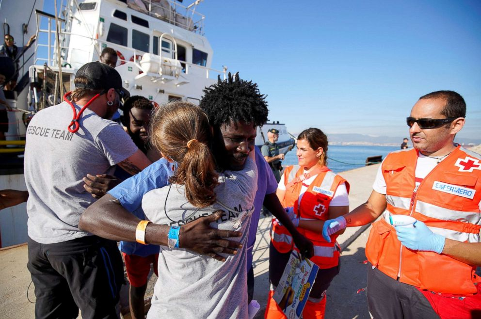 PHOTO: Migrants rescued by NGO Proactiva Open Arms rescue boat in central Mediterranean Sea embrace Open Arms members after arriving at the port of Algeciras in San Roque, southern Spain, Aug. 9, 2018.