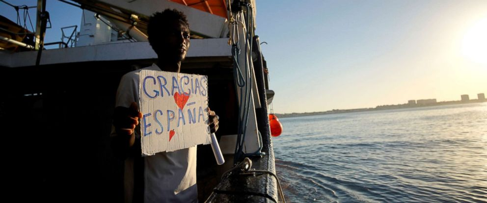 "PHOTO: A migrant rescued by NGO Proactiva Open Arms rescue boat in central Mediterranean Sea holds a placard that reads ""thank you Spain"" on board before arriving at the port of Algeciras in San Roque, southern Spain, Aug. 9, 2018."
