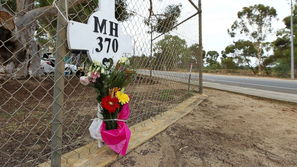Flowers and a memorial for the missing passengers of flight MH370 are attached to the perimeter fence of RAAF Pearce Airbase on March 26, 2014 in Bullsbrook, 35km north of Perth, Australia.