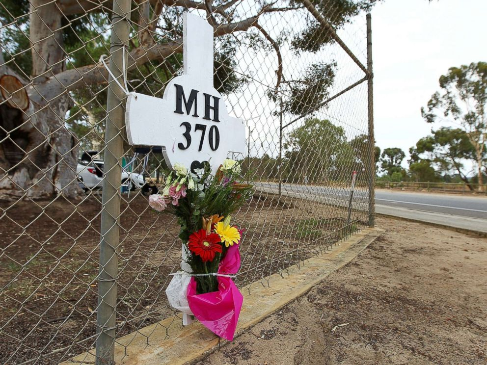 PHOTO: Flowers and a memorial for the missing passengers of flight MH370 are attached to the perimeter fence of RAAF Pearce Airbase on March 26, 2014 in Bullsbrook, 35km north of Perth, Australia.