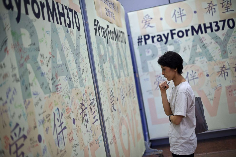 PHOTO: A woman reads prayers and well-wishes on a wall for passengers onboard missing Malaysia Airlines (MAS) flight MH370 during a mass prayer in Kuala Lumpur on April 6, 2014.