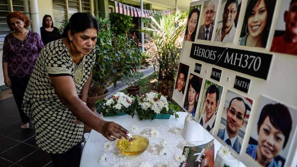 """A school teacher lights a candle as she prays for passengers of missing Malaysia Airlines flight MH370 in Petaling Jaya on March 8, 2016. Malaysia and Australia said they remained """"hopeful"""" of solving the mystery of flight MH370 as the second anniversary of the plane's disappearance arrived on March 8 with no end in sight for devastated families."""