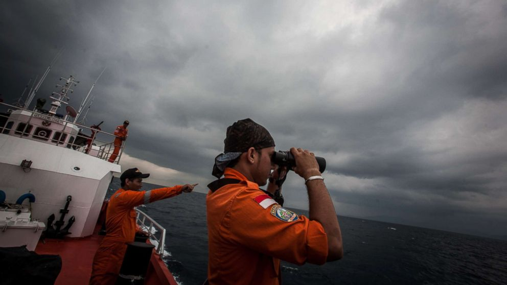 Indonesian national search and rescue agency personel watch over high seas during a search operation for missing Malaysia Airlines flight MH370 in the Andaman Sea on March 15, 2014.