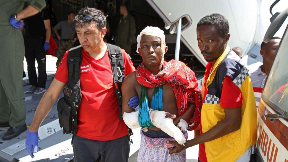 Turkish and Somali paramedics help a wounded man to a Turkish military plane transporting the injured to Turkey at the Mogadishu airport, Oct. 16, 2017, after a truck bomb explosion in the Somali capital. The attack left more than 200 people dead.