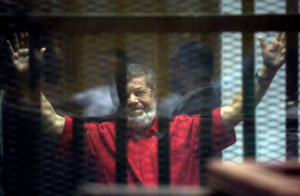 PHOTO: Former Egyptian President Mohammed Morsi raises his hands inside a defendants cage in a makeshift courtroom at the national police academy, in an eastern suburb of Cairo, Egypt, June 18, 2016.