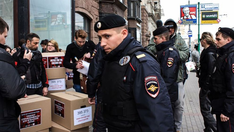 Russian policemen surround Russian gay-rights activists standing next to boxes allegedly containing signed petitions calling for a probe into a reported crackdown on Chechnya's LGBT community, during a rally in central Moscow on May 11, 2017.