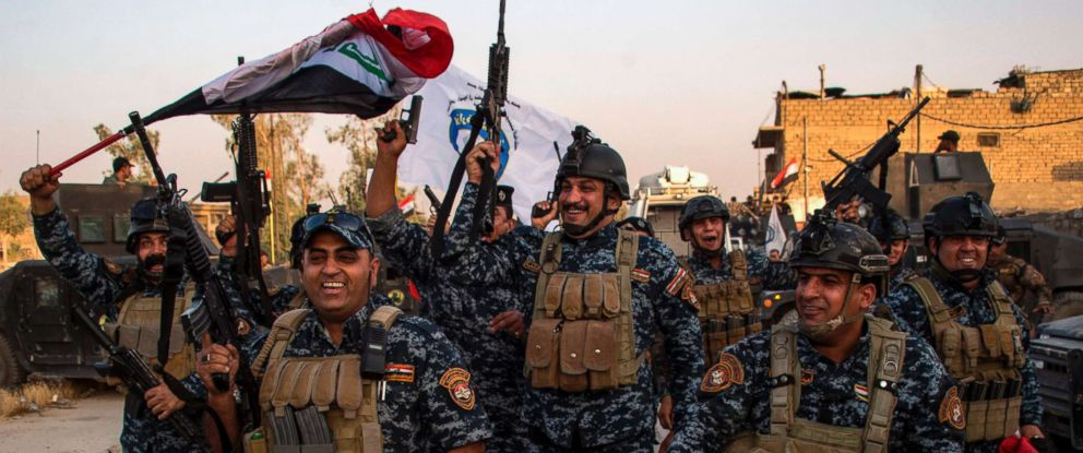 """PHOTO: Members of the Iraqi federal police forces celebrate in the Old City of Mosul, July 10, 2017, after the governments announcement of the """"liberation"""" of the embattled city from Islamic State (IS) group fighters."""