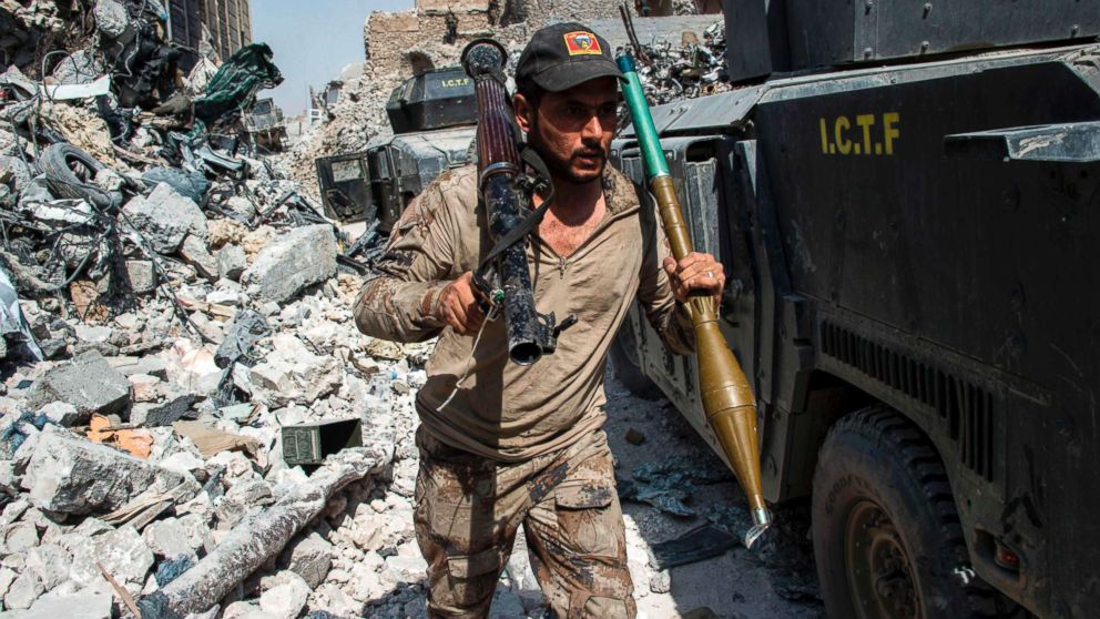 A member of the Iraqi forces walks through the rubble past humvees as he carries a rocket-propelled grenade and launcher in the Old City of Mosul, July 10, 2017, during the offensive to retake the embattled city from Islamic State (IS) group fighters.
