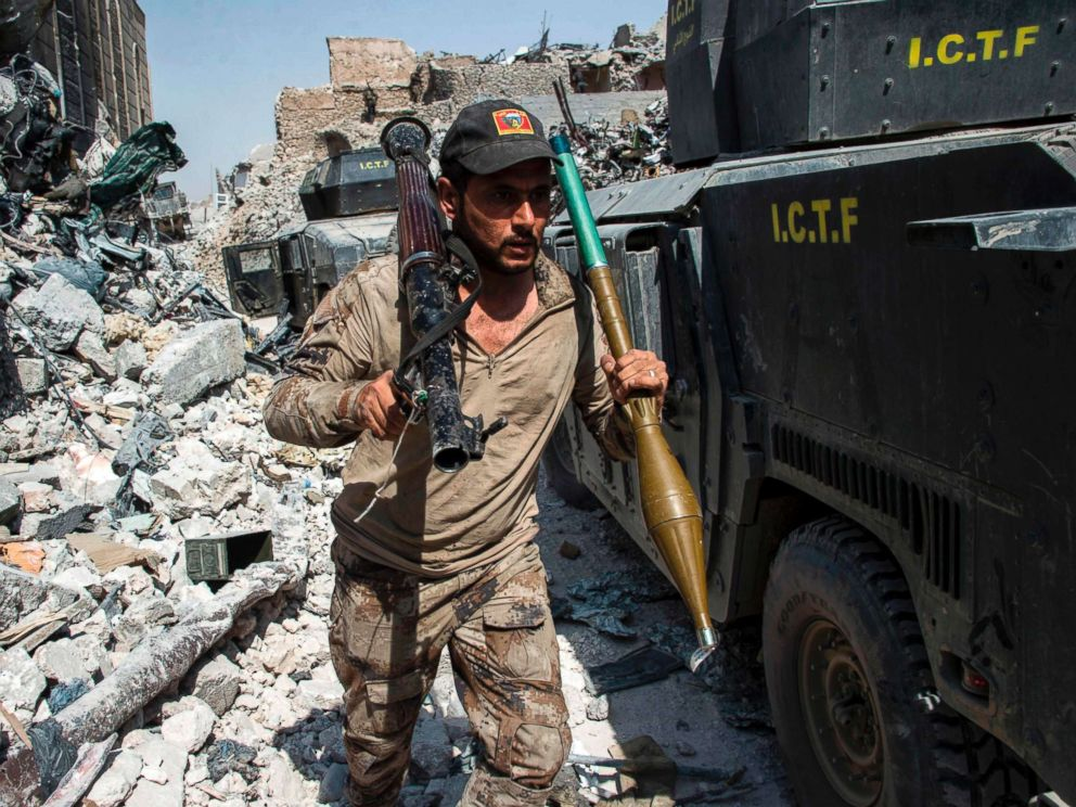 PHOTO: A member of the Iraqi forces walks through the rubble past humvees as he carries a rocket-propelled grenade and launcher in the Old City of Mosul, July 10, 2017.