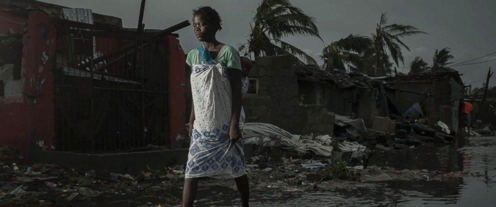 PHOTO: A woman walks through the flooded streets of the city of Beira, Sofala Province, Mozambique, after Cyclone Idai made land fall, March 17, 2019.