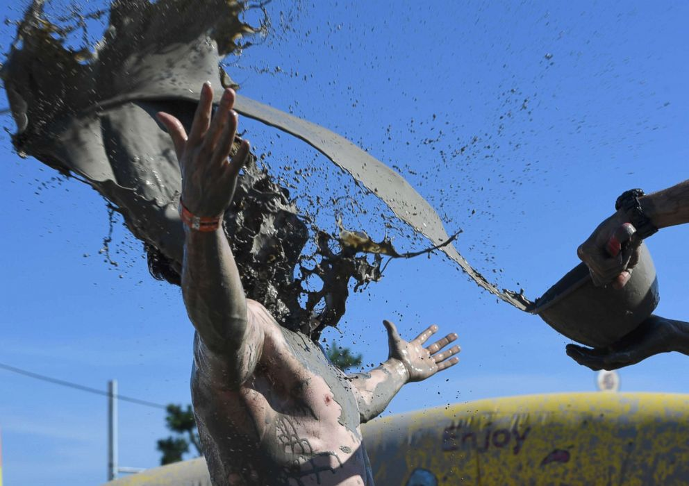PHOTO: A man gets mud thrown onto him by his friend during the 21th Boryeong Mud Festival at Daecheon beach in Boryeong, July 14, 2018.