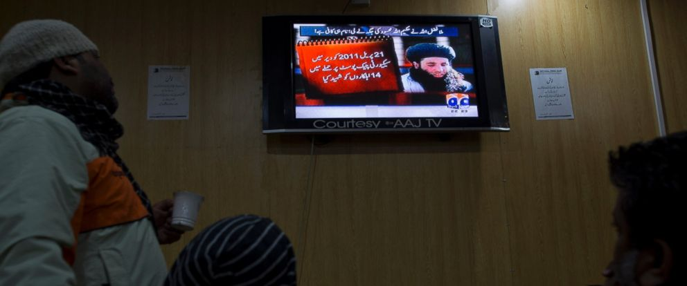 In this Nov. 7, 2013 file photo, people watch a news report about newly selected leader of Pakistani Taliban leader Mullah Fazlullah in Islamabad, Pakistan. An Afghan defense ministry official says June 15, 2018 a US drone strike killed Fazlullah.