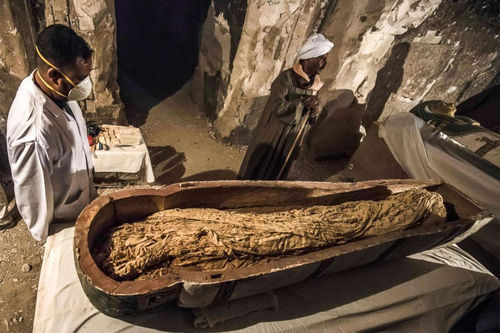 PHOTO: Egyptian workers and archaeologists standing next to an opened intact sarcophagus containing a well-preserved mummy of a woman named Thuya wrapped in linen, discovered by a French mission at the site of Tomb TT33, Nov. 24, 2018.