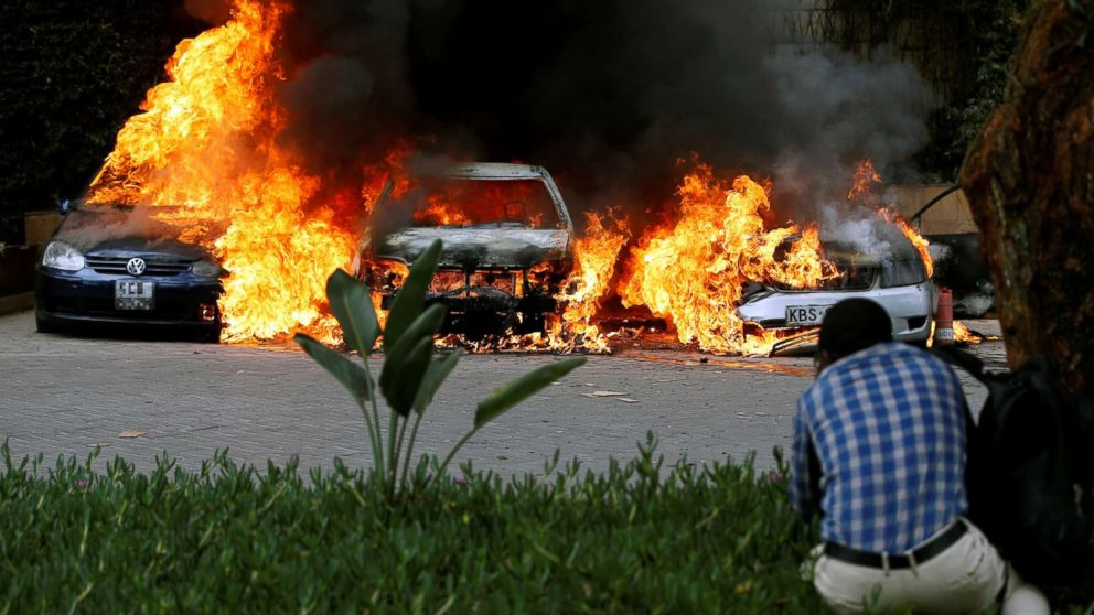 Cars are seen on fire at the scene of explosions and gunshots in Nairobi, Kenya, Jan. 15, 2019.