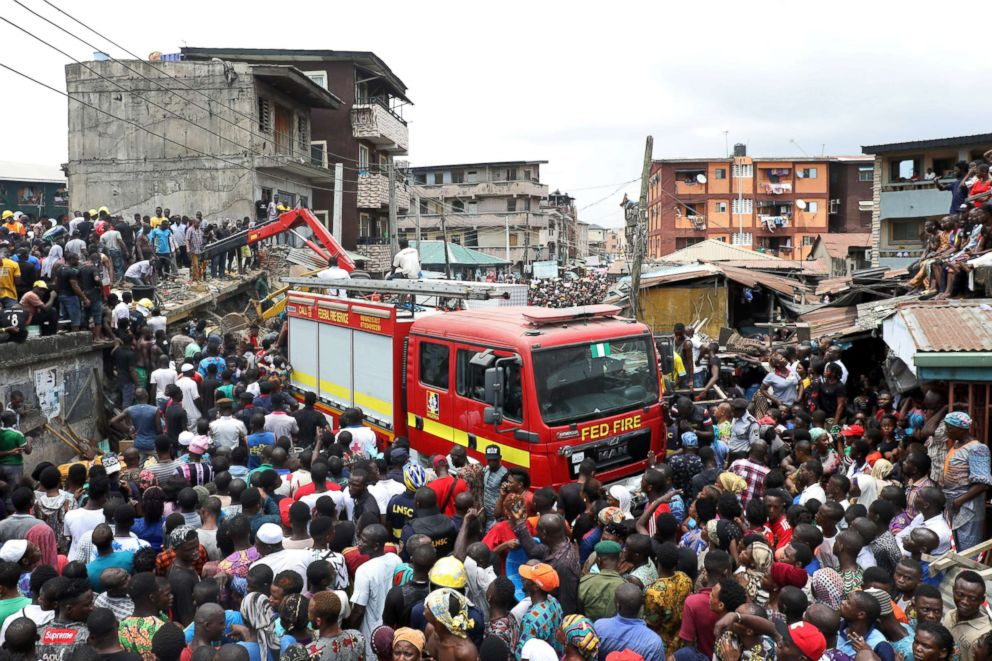PHOTO: People gather as rescue workers search for survivors at the site of a collapsed building containing a school in Nigerias commercial capital of Lagos, Nigeria, March 13, 2019.