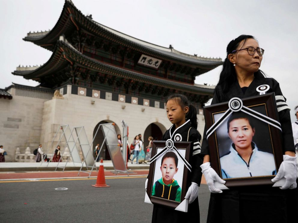 PHOTO: A girl and her North Korean defector mother hold portraits of a 42-year-old defector mother and her 6-year-old son who were found dead in starvation as they march during their funeral in Seoul, South Korea, Sept. 21, 2019.