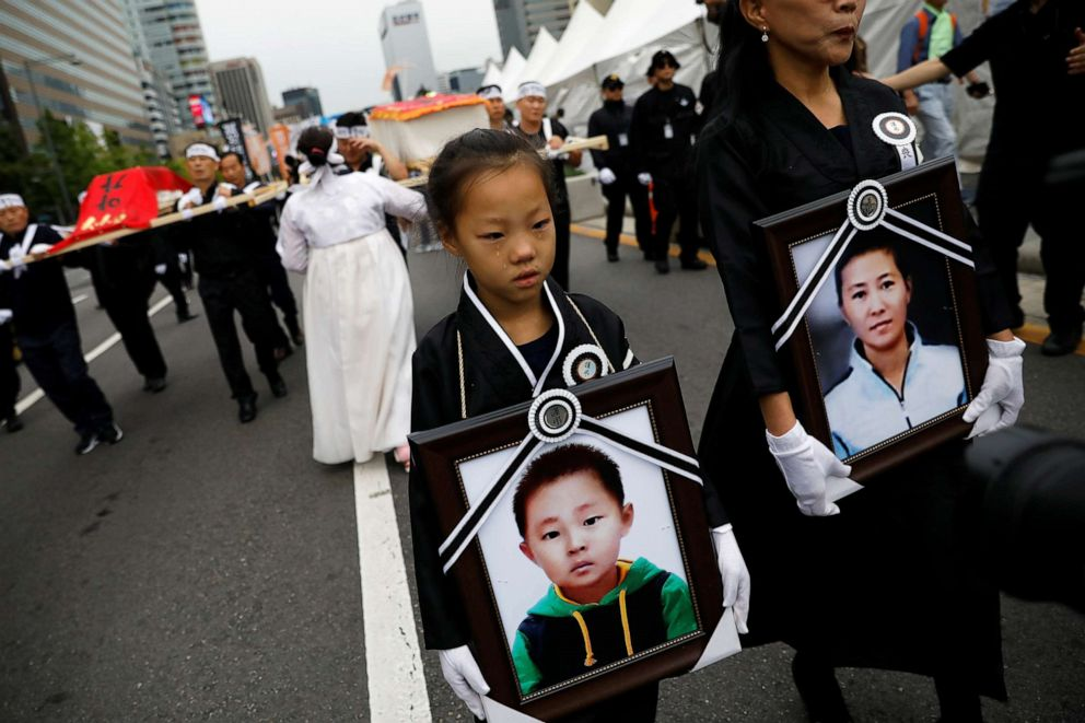 PHOTO: A girl and her North Korean defector mother hold portraits of a 42-year-old defector mother and her 6-year-old son who were found dead of starvation in Seoul, South Korea, Sept. 21, 2019.