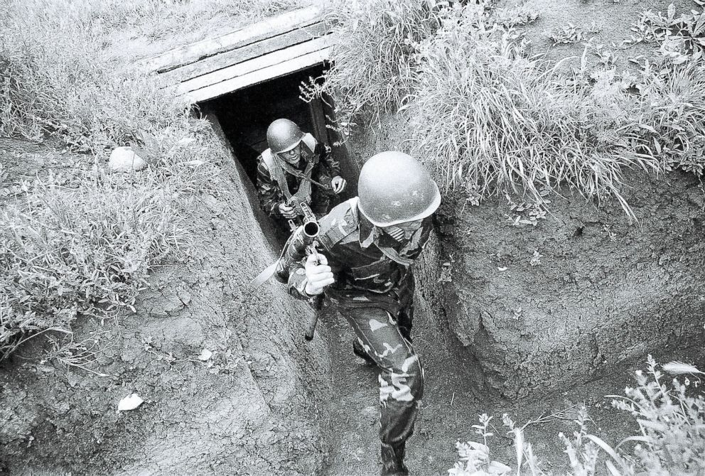 PHOTO: A pair of NKR soldiers are rushing out of their bunker during an Azeri sniper attack.