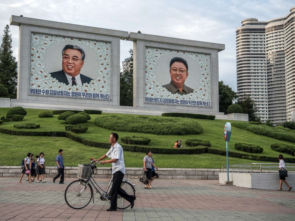 PHOTO: People walk past pictures of Kim Il-sung and Kim Jong-il on Aug. 18, 2018 in Pyongyang, North Korea.