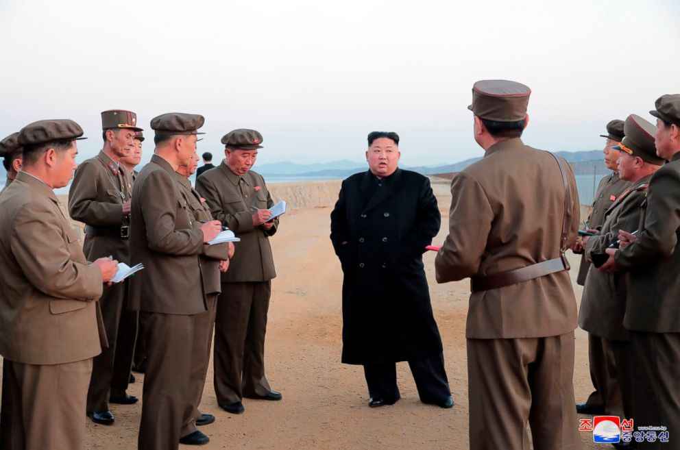In this undated photo released by the North Korean government on Nov. 16, 2018, North Korean leader Kim Jong Un listens to a military official as he inspects a weapon testing at the Academy of National Defense Science, North Korea.
