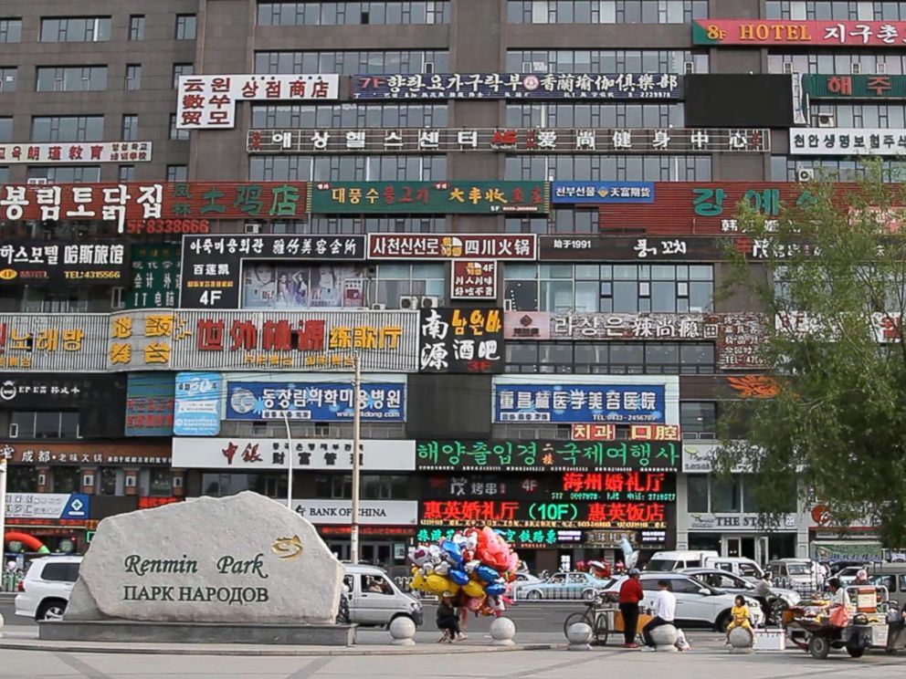 PHOTO: Signs in both Chinese and Korean can be seen on the side of building across from the Peoples Park or Renmin Park in Yanji, China, the largest city in Chinas Yanbian Korean Autonomous Prefecture.