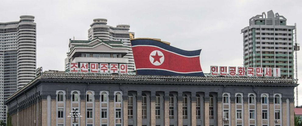 PHOTO: Women walk across Kim Il-sung Square as a huge North Korea flag is displayed atop the Central Committee of the Workers Party of Korea building, Aug. 23, 2018, in Pyongyang, North Korea.