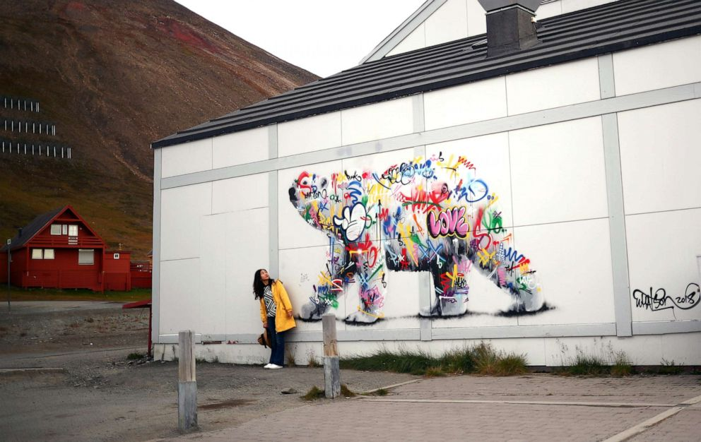 PHOTO: A woman poses next to a polar bear mural in the town of Longyearbyen in Svalbard, Norway, Aug. 6, 2019.