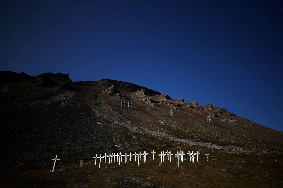 PHOTO: White wooden gravestones at risk of landslides due to the thawing permafrost underneath the ground, stand at the side of a mountain in the Longyearbyen cemetery in the town of Longyearbyen in Svalbard, Norway, Aug. 3, 2019.