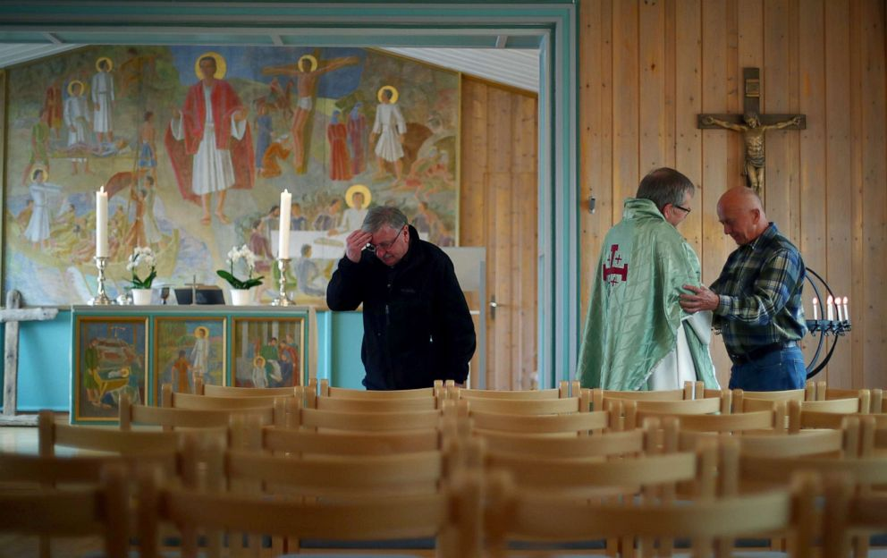 PHOTO: Interim Vicar, Ivar Smedsrod consoles Polish visitor Wieslaw Sawicki after a mass at the Svalbard Church in the town of Longyearbyen, in Svalbard, Norway, Aug. 4, 2019.