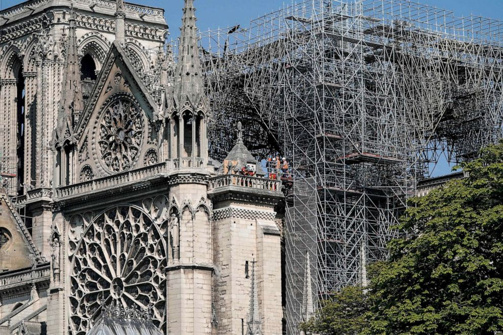 PHOTO: Firefighters and technicians work on a balcony of Notre-Dame de Paris Cathedral in Paris, April 19, 2019, four days after a fire devastated the cathedral.