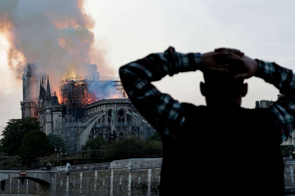 A man watches Notre-Dame Cathedral burn in Paris, April 15, 2019.