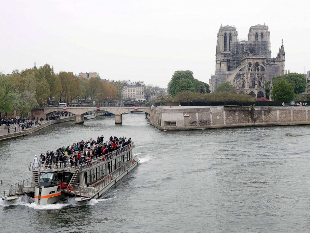 PHOTO: A tourist boat sails on the river Seine near Notre-Dame-de-Paris on April 16, 2019 in the aftermath of a fire that devastated the cathedral.