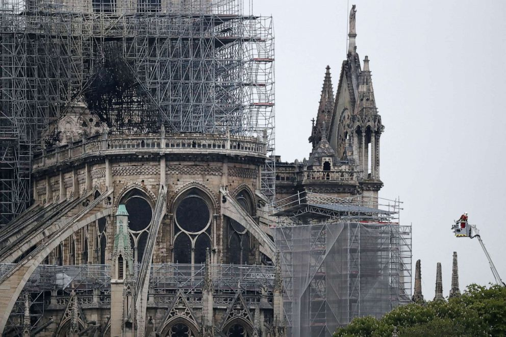 PHOTO: A firefighter stands in an aerial lift near the burnt roof after a massive fire destroyed the roof of the Notre-Dame Cathedral in Paris, April 16, 2019.