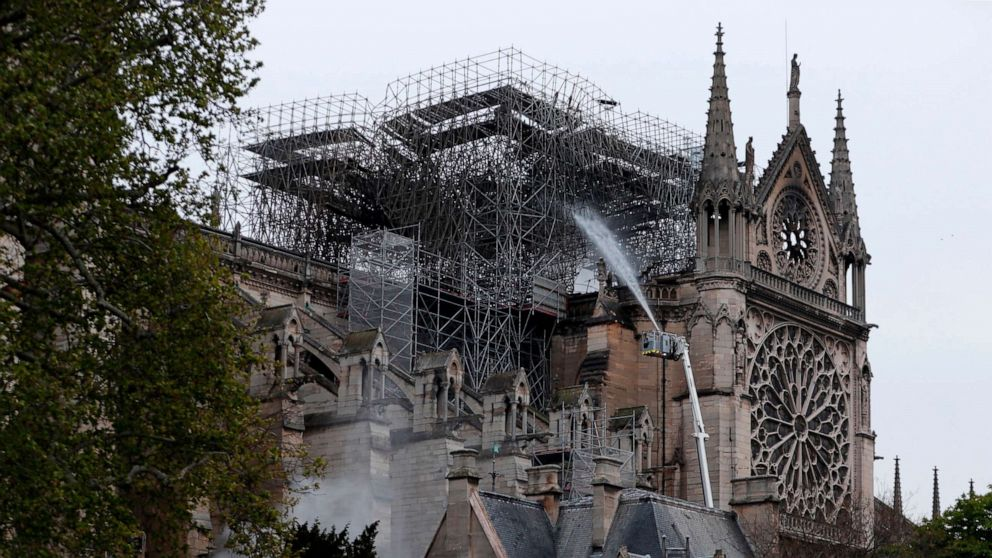 Firefighters spray water as they work to extinguish a fire at Notre-Dame Cathedral in Paris early on April 16, 2019.