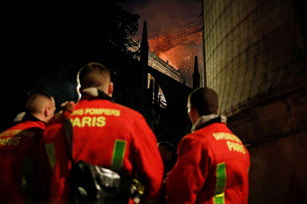 Firefighters watch the flames billowing from the roof at Notre Dame Cathedral in Paris on April 15, 2019.