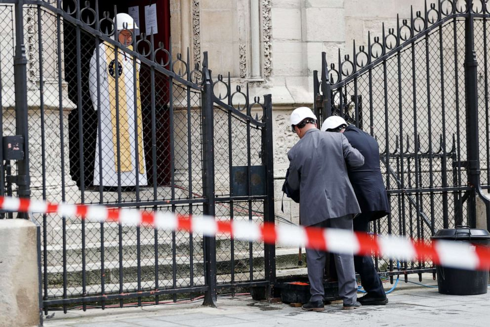 PHOTO: TOPSHOT - Notre-Dame de Paris cathedrals rector Patrick Chauvet greets people arriving for the first mass of the Notre-Dame de Paris cathedral two months after the fire, on June 15, 2019 in Paris.