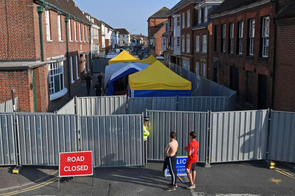 PHOTO: Work goes on behind the barriers across Rollestone Street, outside the John Baker House Sanctuary Supported Living in Amesbury, southern England, July 5, 2018, in connection with the investigation after a man and woman were found unconscious.