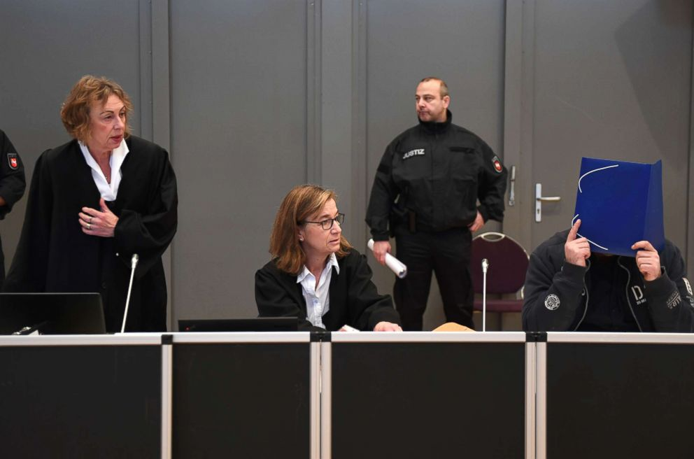 Niels Hoegel (R), sits next to his lawyers Ulrike Baumann (C) and Kirsten Huefken (L), after he arrives for the first day of his trial, Oct. 30, 2018 in Oldenburg, Germany.