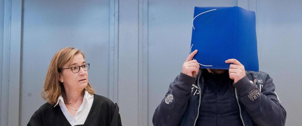 PHOTO: Former nurse Niels Hoegel, is accused of killing more than 100 patients in his care, hides behind a folder as he arrives in the courtroom, Oct. 30, 2018, in Oldenburg, Germany, for the start of his trial.