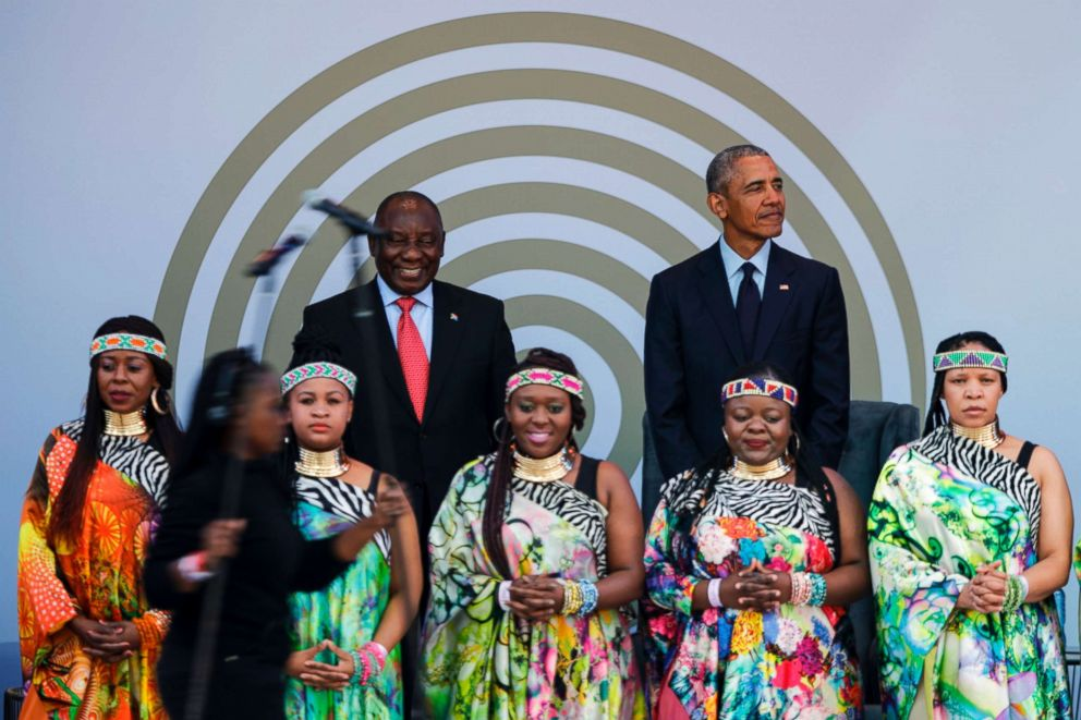 PHOTO: South African President Cyril Ramaphosa and former President Barack Obama stand on stage behind the Soweto Gospel Choir, during the 2018 Nelson Mandela Annual Lecture at the Wanderers cricket stadium in Johannesburg, July 17, 2018.