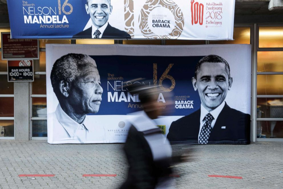 PHOTO: A person walks past a banner depicting former South African leader Nelson Mandela and former president Barack Obama outside the Wanderers cricket stadium in Johannesburg, July 17, 2018, where Obama will deliver the Nelson Mandela Annual Lecture.