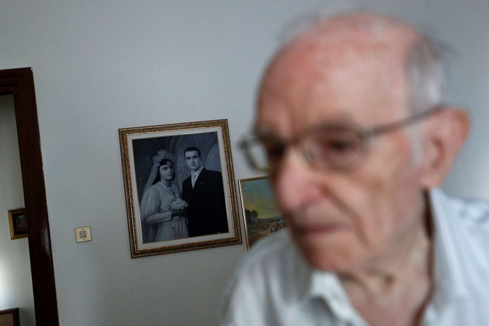 PHOTO: Giuseppe Paterno, 96, Italy's oldest student, walks past a painting hung on the wall depicting his wedding day with his late wife Stefana Battaglia, who died in 2006, and Paterno, two days before he graduates from The University of Palermo.