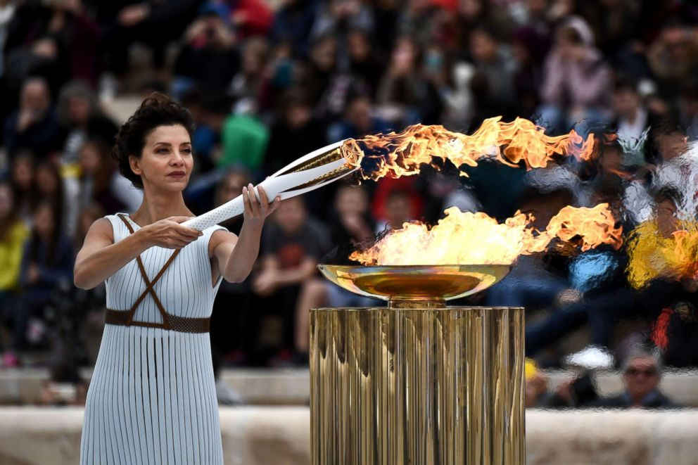 PHOTO: Actress Katerina Lechou, playing a high priestess lights a torch at The Panathenaic Stadium in Athens on October 31, 2017, during the handover ceremony of the Olympic flame for the 2018 Winter Olympics in Pyeongchang, South Korea.
