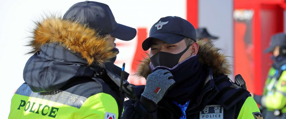 PHOTO: Two police officers protect their face from the cold at the Olympic stadium of the Pyeongchang Winter Olympic Games in Pyeongchang, South Korea Feb. 7, 2018.
